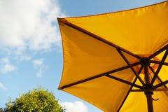 Paraguas de sol amarillo con el cielo en fondo Fotos de archivo libres de regalías