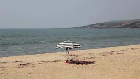 Paraguas de sol rayado en una playa arenosa en el fondo del océano con las ondas del mar debajo de un cielo azul claro almacen de metraje de vídeo