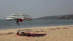 Paraguas de sol rayado grande en el viento en una playa arenosa contra el océano con las ondas del mar debajo de un cielo azul cl almacen de metraje de vídeo