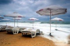 Paraguas de Sun aislado en una playa inundada Fotografía de archivo