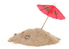Paraguas del cóctel en montón de la arena con las cáscaras Fotografía de archivo libre de regalías