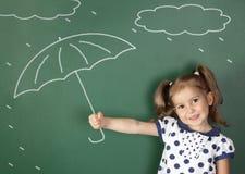 Paraguas del control de la muchacha del niño cerca de la pizarra de la escuela, concepto del tiempo imagen de archivo libre de regalías
