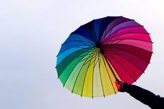 Paraguas a disposición contra fondo del cielo Imagen de archivo