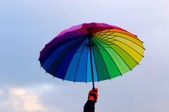 Paraguas a disposición contra fondo del cielo Foto de archivo