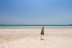 Paraguas doblado en la playa Imagen de archivo