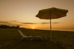 Paraguas en la playa en la puesta del sol Fotografía de archivo