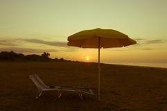 Paraguas en la playa en la puesta del sol Fotos de archivo libres de regalías