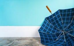 Paraguas en piso del cemento con el fondo en colores pastel de la pared Fotografía de archivo libre de regalías