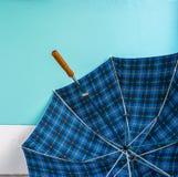Paraguas en piso del cemento con el fondo en colores pastel de la pared Imagen de archivo libre de regalías