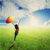 Paraguas feliz del salto y del control de la mujer en cielo verde de los campos y de las nubes del arroz Fotografía de archivo libre de regalías