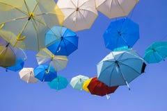 Paraguas flotantes con el fondo del cielo azul Imágenes de archivo libres de regalías