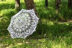 Paraguas hecho punto, blanco en hierba verde imagenes de archivo