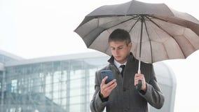 Paraguas joven de la tenencia del hombre de negocios y usar un teléfono elegante en a fotos de archivo libres de regalías