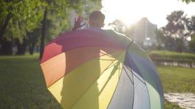 Paraguas multicolor que miente en la hierba en el parque Poco muchacho despreocupado que salta de detrás un paraguas y metrajes
