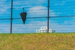Paraguas negro en la cerca Imagen de archivo libre de regalías
