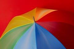 Paraguas Particoloured en fondo rojo Fotos de archivo