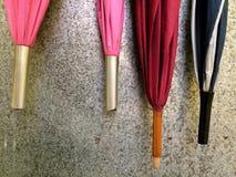 Paraguas que cuelgan en la pared superficial metálica Foto de archivo