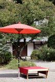 Paraguas rojo en jardín Imagen de archivo libre de regalías