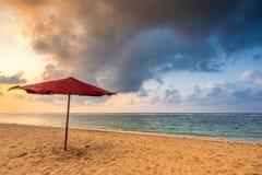 Paraguas rojo en una playa Fotos de archivo