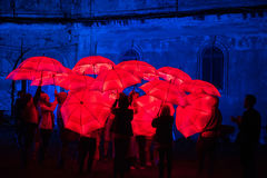 Paraguas rojo iluminado por las lámparas llevadas en la noche Imágenes de archivo libres de regalías