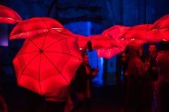 Paraguas rojo iluminado por las lámparas llevadas en la noche Fotos de archivo