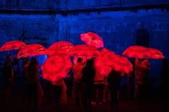Paraguas rojo iluminado por las lámparas llevadas en la noche Foto de archivo