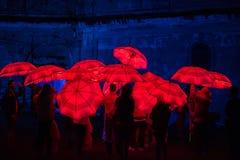 Paraguas rojo iluminado por las lámparas llevadas en la noche Imagen de archivo libre de regalías