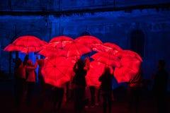 Paraguas rojo iluminado por las lámparas llevadas en la noche Fotografía de archivo libre de regalías
