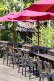 Paraguas rojo, sillas de madera y tabla en café vacío al lado del mar en la playa tropical, Tailandia Imagen de archivo libre de regalías