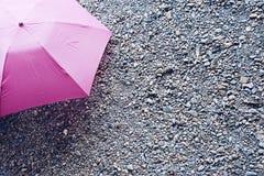 Paraguas rosado en la tierra de la roca Fotografía de archivo