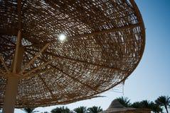 Paraguas trenzados en el cielo azul con el sol y las palmas Sol a través de la bóveda de la rota del parasol de playa y del cielo Foto de archivo libre de regalías