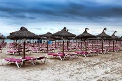 Paraguas tropicales de la paja en una playa abandonada en un weathe desagradable Imagen de archivo