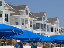 Paraguas y casas de playa imagenes de archivo
