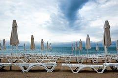 Paraguas y deckchairs cerrados en la playa vacía Fotografía de archivo libre de regalías