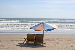 Paraguas y dos sillas en la playa Fotografía de archivo libre de regalías