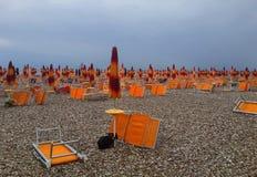 Paraguas y salones anaranjados de la calesa en la playa de Fano en Ital Fotografía de archivo