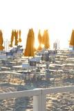 Paraguas y sillas, bañando el establecimiento en el amanecer Imagen de archivo