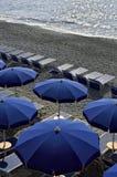 Paraguas y sillas en una playa imagenes de archivo
