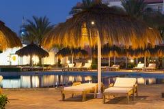 Paraguas y sunbeds de la paja por la piscina en Sharm el Sheikh Foto de archivo