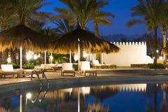 Paraguas y sunbeds de la paja por la piscina en Sharm el Sheikh Fotografía de archivo