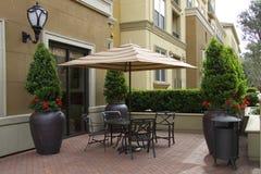 Paraguas y tabla acogedores del patio con las sillas Fotografía de archivo
