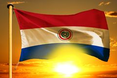 Paraguay flag weaving on the beautiful orange sunset with clouds background. Paraguay flag weaving on the beautiful orange sunset background royalty free stock photography