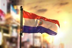 Paraguay flagga mot suddig bakgrund för stad på soluppgång Backlig royaltyfria foton