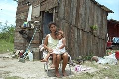 Paraguayan mother and child live in great poverty. Paraguay, capital, city Asuncion: Young woman with her daughter in front of their house in the slum Banjado royalty free stock photos