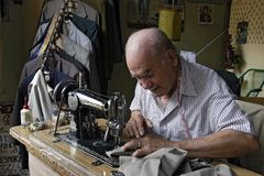 Paraguayan Senior tailor is sewing in dressmaking royalty free stock photo