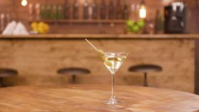 Parallax shot of a martini glass on an empty wooden table with bar counter on the background. Martini beverage with olives as garnish stock video footage