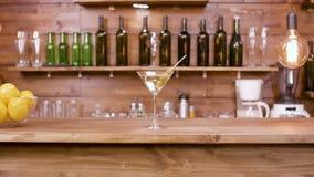 Parallax sköt av ett exponeringsglas av den martini drycken på en stångbakgrund stock video