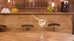 Parallax sköt av ett martini exponeringsglas på en tom trätabell med stångräknaren på bakgrunden lager videofilmer