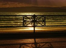 Parallel bars. Of the fence of the promenade at sunset stock photography