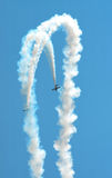 Parallel Diving Stunt Planes. Two stunt planes make a synchronized dive while trailing smoke at an air show demonstration Stock Photos